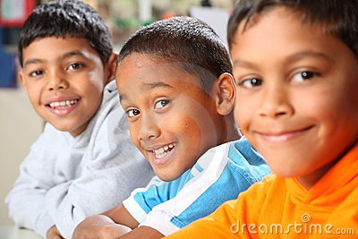 Row of three smiling young school boys in class