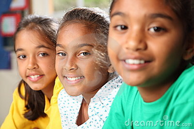 Row of three smiling young school girls