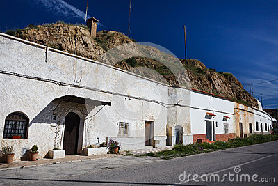 Row of whitewashed hillside cave houses in Gaudix