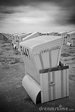 Rows of abandoned roofed wicker beach chairs