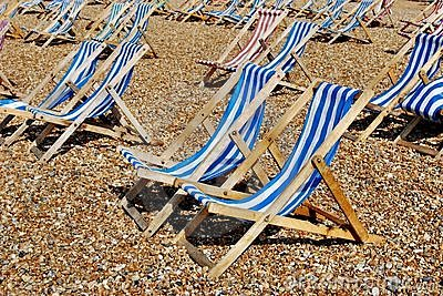 Rows of empty traditional deckchairs on beach
