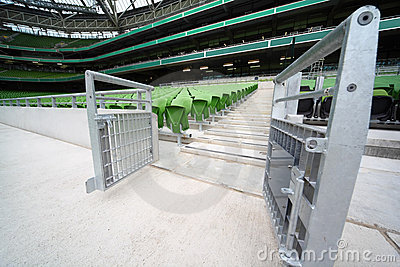 Rows of folded, green seats in empty stadium