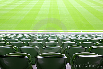 Rows of folded plastic seats in empty stadium