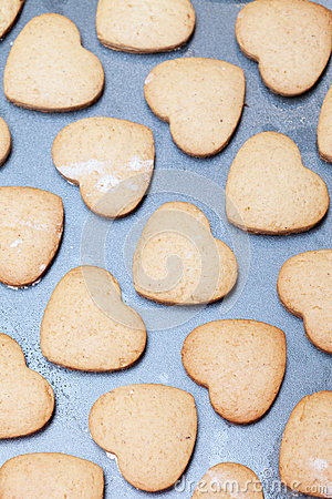 Rows of heart shaped biscuits on metal baking tray