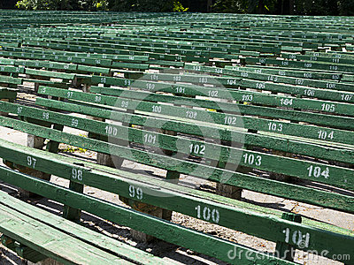 Rows of simple green seats near empty outdoors scene