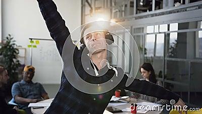 Rozochocony i szczęśliwy biznesmen aktywnie tanczy podczas gdy słuchający muzykę na biurze obok koledzy Jest ubranym zbiory wideo