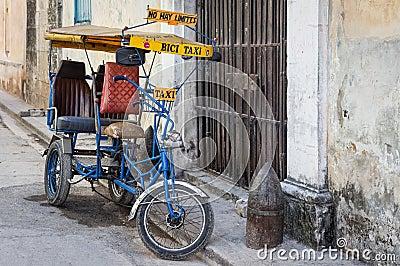 Rua em Havana com uma bicicleta velha e umas construções gastos