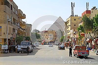 Ruas do Cairo com as grandes pirâmides de Giza Foto Editorial