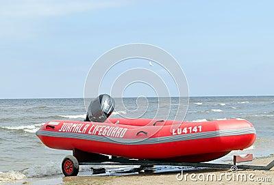Rubber lifeguard boat trailer on sea shore
