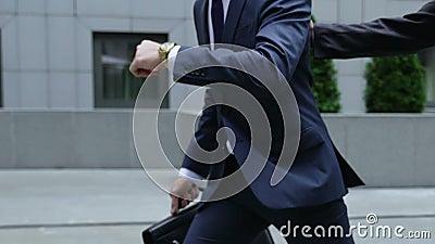 Ruchliwie mężczyzna sprawdza czas w zegarkach, śpieszy biura centrum, kolega outruns on zbiory wideo