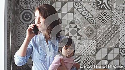 Ruchliwie poważny macierzysty mienie jej dziecko i opowiadać na smartphone zbiory