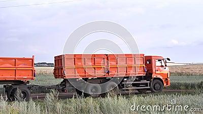 Ruck arancio e nuovo con il rimorchio che si muove sulla strada campestre sul fondo verde e giallo del campo scena Camion con un  video d archivio