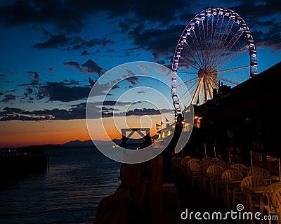 Rueda de Ferris en el agua en la puesta del sol