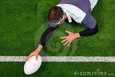 Rugby player scoring a try with one hand