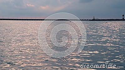 Ruhiges Meerwasser bei Sonnenuntergang im Sommer, Sonnenreflexion auf der Wasseroberfläche mit kleinen Wellen, Pier und Leuchttur stock video
