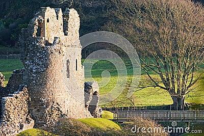 Ruinas viejas del castillo con el Lit del puente en la puesta del sol