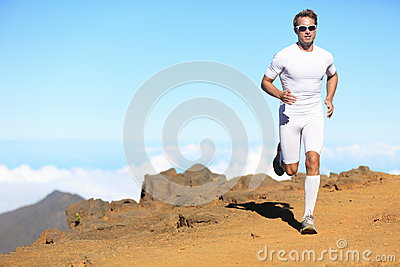 Runner man trail running in scenic landscape nature in compression
