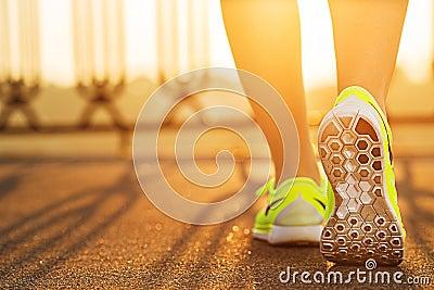 Runner woman feet running on road closeup on shoe. Female fitness model sunrise jog workout. Sports lifestyle concept. Stock Photo