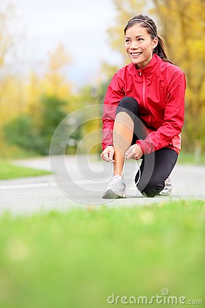 Runner woman tying running shoes