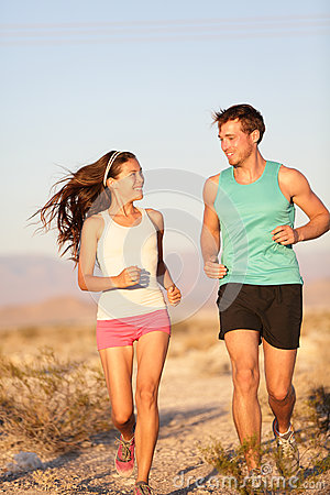 Runners - Active fitness couple running laughing