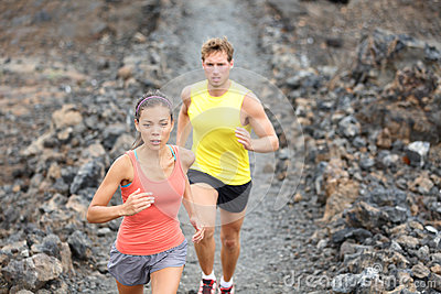 Runners couple running on trail in cross country