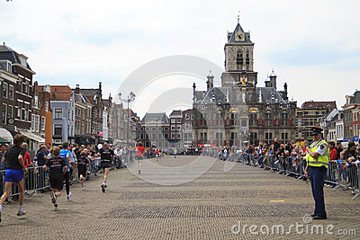 Runners passing city hall in historic Delft Editorial Stock Image