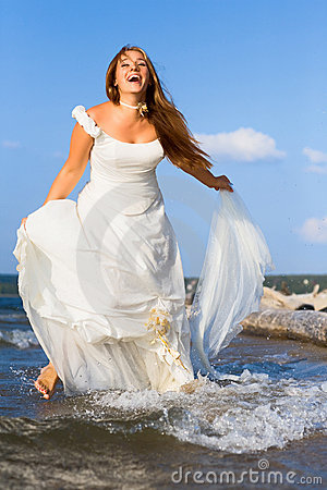 Running laughing bride on the sea