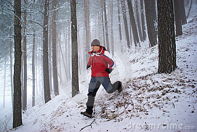 Running man in winter mountain forest