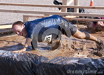 Running, Mud, and Obstacle Course Editorial Stock Image