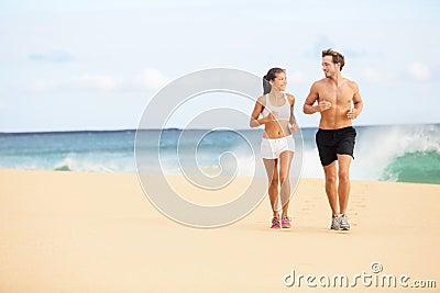Running people - runners couple on beach run