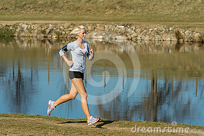 Running woman outdoor sport by river bank