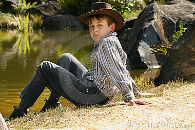 Rural boy sitting by riverbank