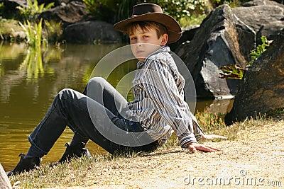 Rural boy sitting by riverbank