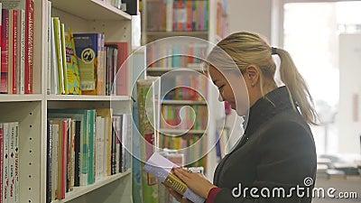 Rusland, Novosibirsk, oktober 2019 Een jonge blond vrouw zoekt een boek op de rekken van een boekhandel Langzame beweging stock footage