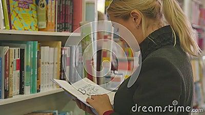 Rusland, Novosibirsk, oktober 2019 Een jonge blond vrouw zoekt een boek op de rekken van een boekhandel Langzame beweging stock video