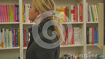 Rusland, Novosibirsk, oktober 2019 Een jonge blond vrouw zoekt een boek op de rekken van een boekhandel Langzame beweging stock videobeelden