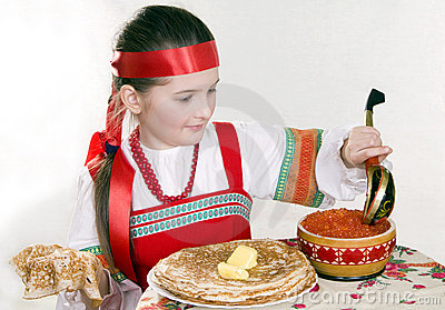 Russian girl eats pancakes with red caviar.