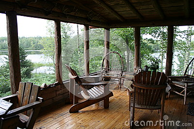 Rustic cabin porch with lake view stock photo image for Vacation home furniture