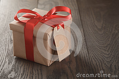 Rustic gift box with red ribbon bow and emmpty tag