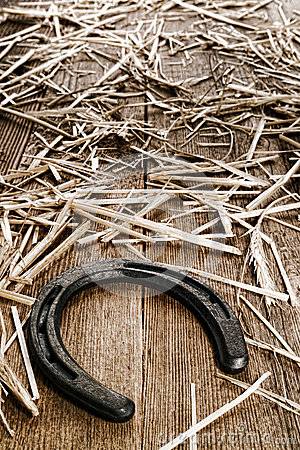 Rustic Horseshoe on Old Wood Barn Floor with Straw