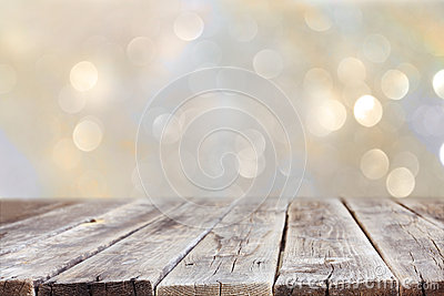 Rustic wood table in front of glitter silver and gold bright bokeh lights Stock Photo