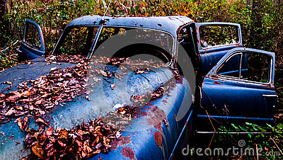 An rusty, abandoned car covered in fallen leaves