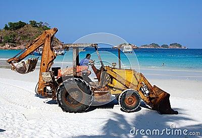 Rusty back hoe on white sand beach