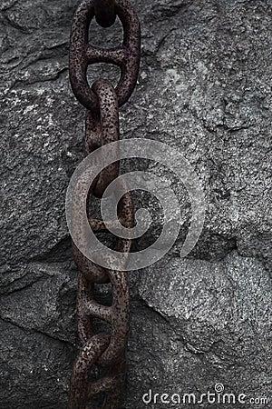 Rusty chain on rock