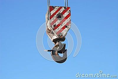 Rusty crane hook hanging on blue sky