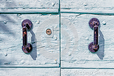 Rusty iron handles on a painted wooden door