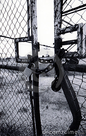 Rusty lock and chain on old bent gate