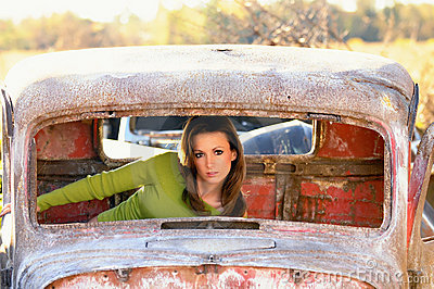 Rusty old auto with young woman inside