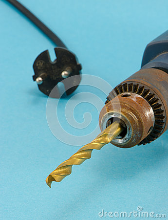 Rusty old electric drill golden bit closeup