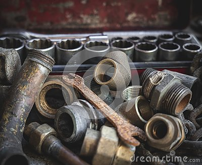 Rusty old plumber pipes with rusty wrench and toolbox Stock Photo